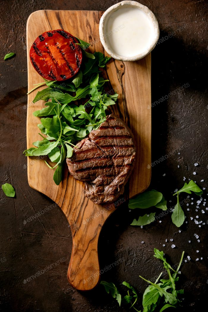 Grilled beef steak served with creamy sauce, grilled vegetables
