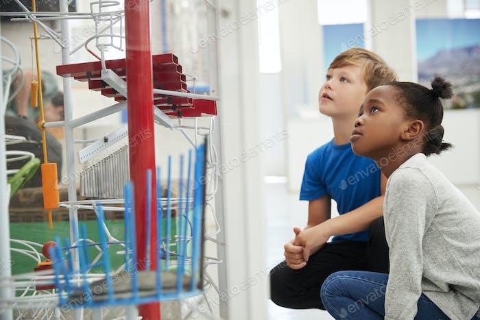 Zwei Kinder kniend und schauen auf eine wissenschaftliche Ausstellung