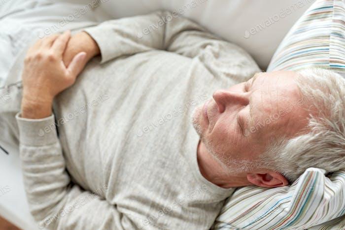 close up of senior man sleeping on sofa