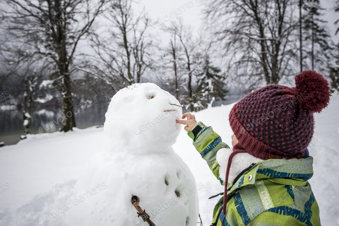 Young child making a winter snowman