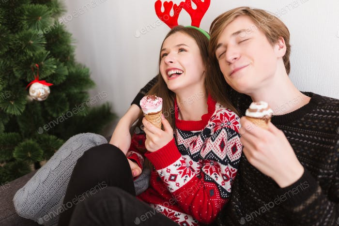 Portrait of young joyful couple having fun at home eating ice-cream at Christmas time