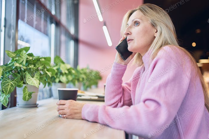 Adalt charming woman calling with cell telephone while sitting alone in coffee shop