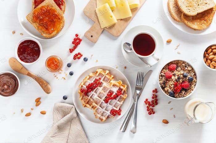 Frühstück mit Müsli Beeren Nüsse, Waffel, Toast, Marmelade, Schokoladenaufstrich und Kaffee. Ansicht von oben