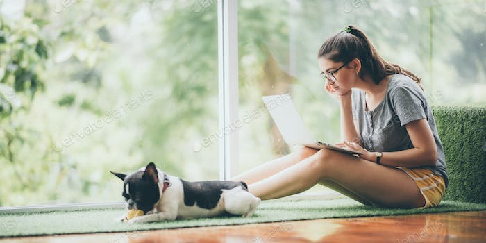 young girl playing a dog at home, cute woman person with her pet animal living from home