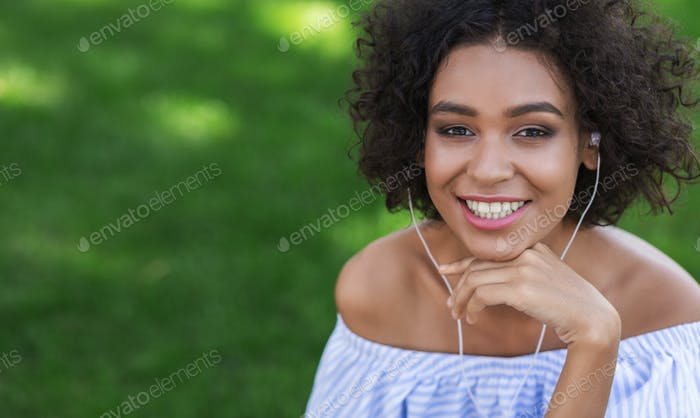 Excited black woman listening to music outdoors