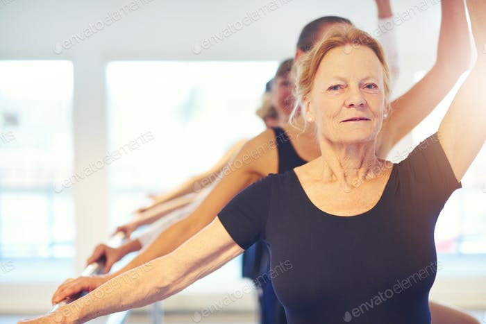 Senior woman performing ballet looking at camera