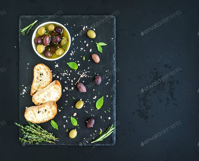 Mediterranean olives with herbs and ciabatta slices on black slate tray