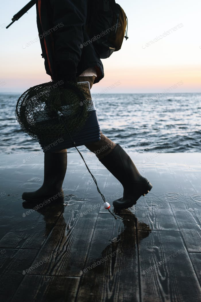 Cropped image of a fisherman wearing coat