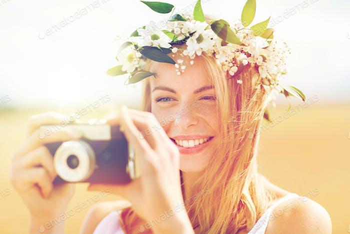 femme heureuse avec caméra de film en couronne de fleurs