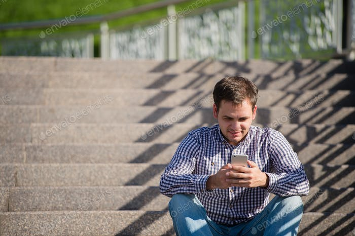 people, style, technology and lifestyle - young man with smartphone sitting on stairs in city