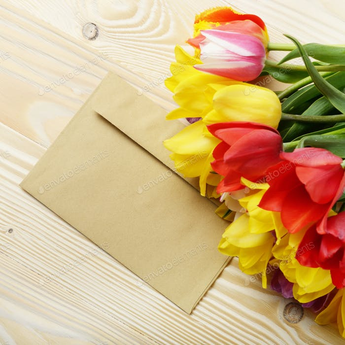 Colorful tulips and blank envelope on natural wooden background
