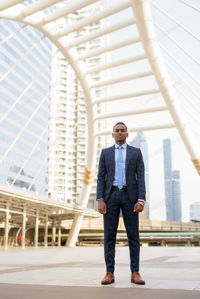 Full body shot of young handsome African businessman wearing suit in the city outdoors