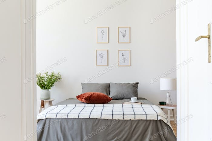 Posters above grey bed with patterned blanket and red pillow in