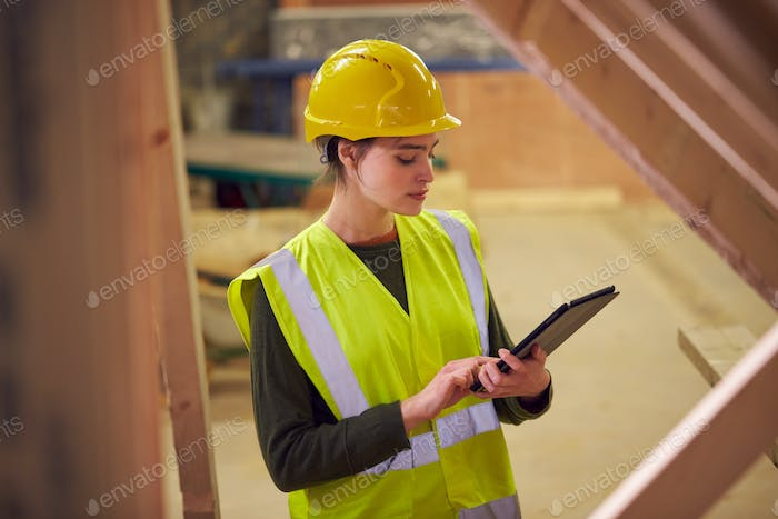 Female Safety Inspector With Digital Tablet At Construction Site