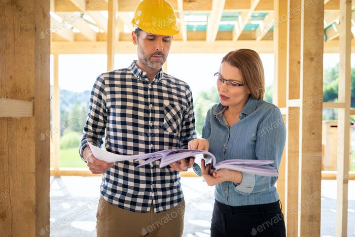 Homeowner consults blueprints with architect or engineer on construction site