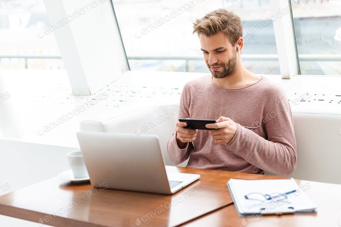 Image of young man wearing earbuds working on laptop in cafe indoors
