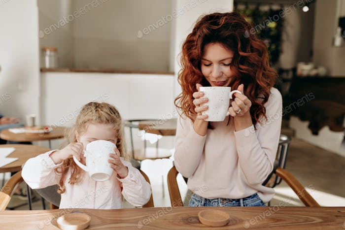 Young mom with her 5 years old daughter sitting in  cafe and drinking cacao in sunlight.