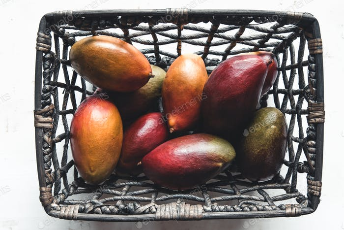 large mangoes in a wicker basket on white background. Healthy food, vegan