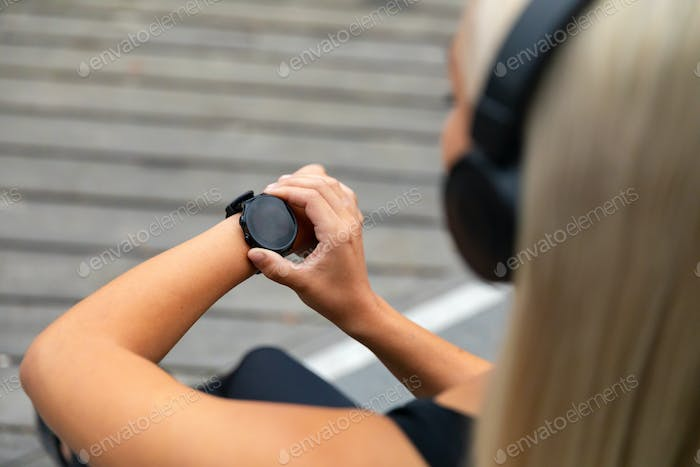 Female runner setting up the fitness smart watch for running