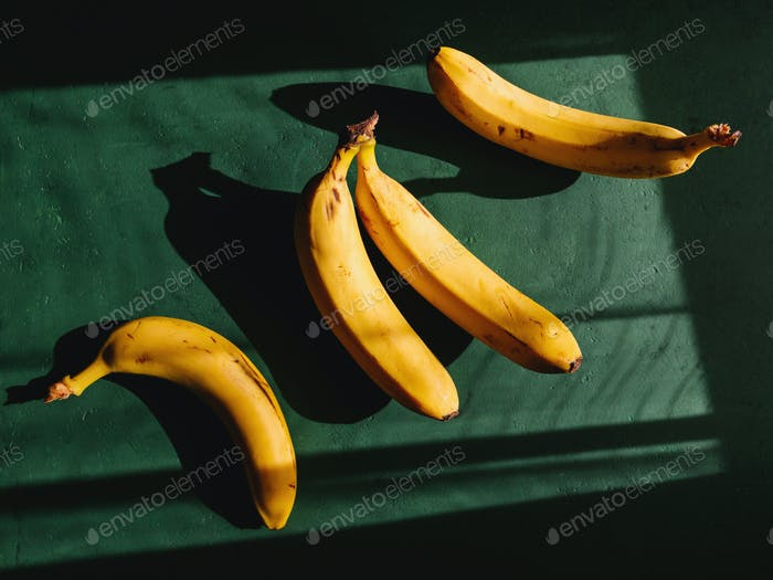 Bananas on a green background. Summer abstract creative photography.