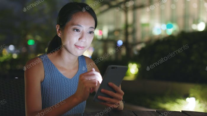 Woman uses smart phone for online