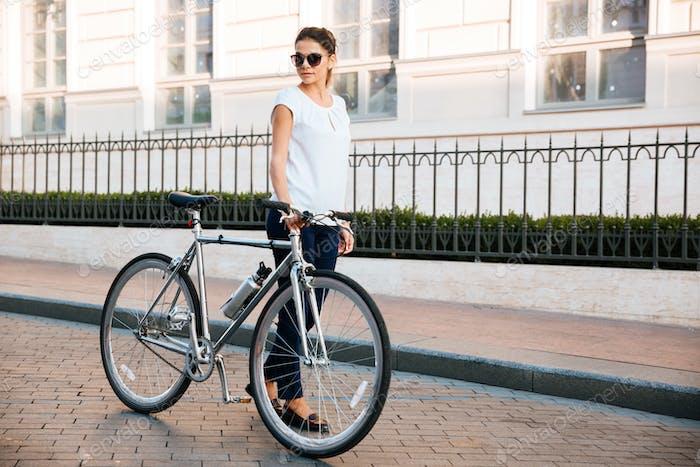 Casual brunette woman cyclist standing near a bike