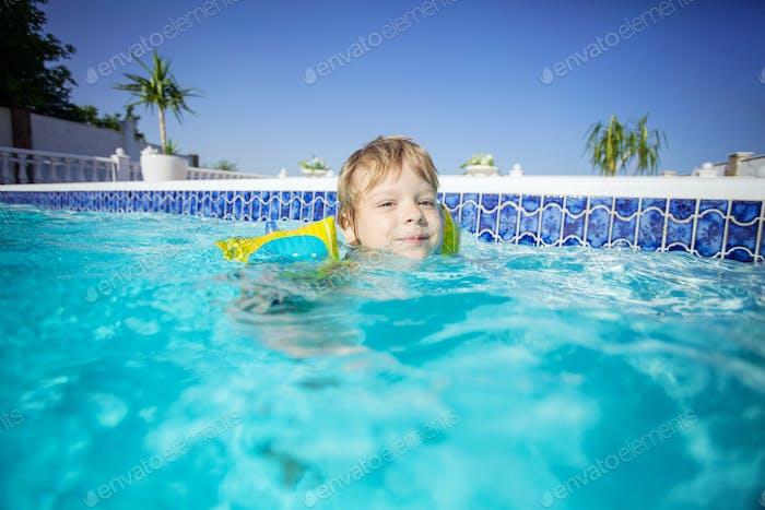 Alegre rubia chico vistiendo flotadores y la natación al aire libre