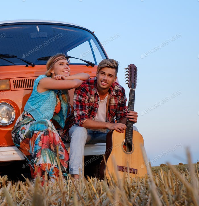 Hippie couple with guitar on a road trip