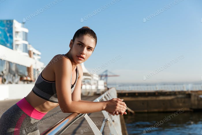 Close-up of attractive female athlete leaning on a handrail and looking at the sea, finish workout