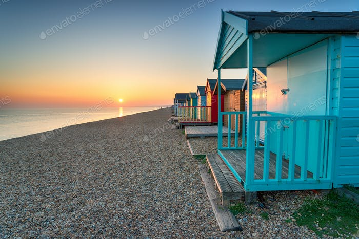 Stunning sunset over seaside beach huts