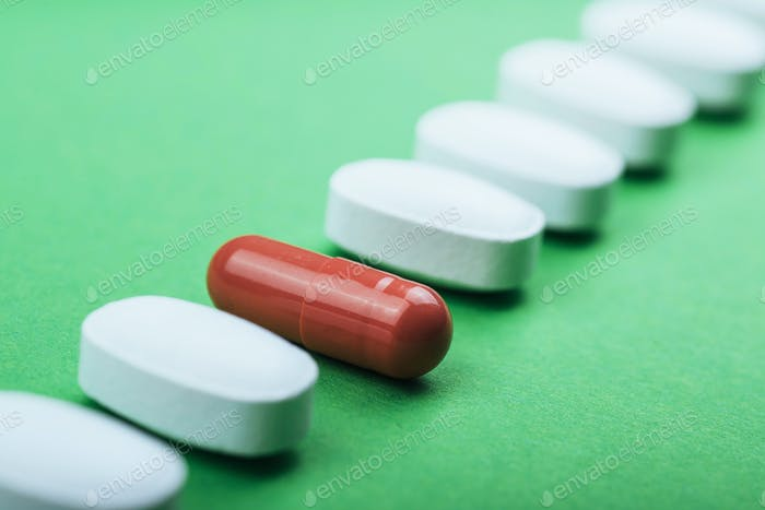 Medical white pills and brown capsules for the treatment and health care on a green background