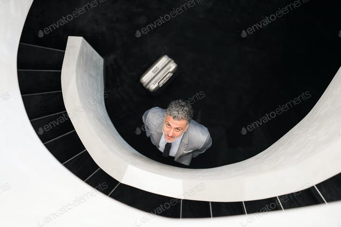 Businessman with suitcase standing at staircase.