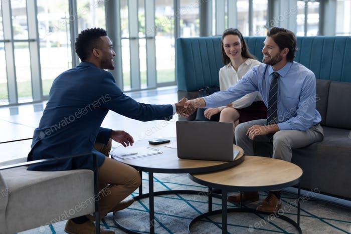Side view of young multi-ethnic business people shaking hands with each other in the lobby at office