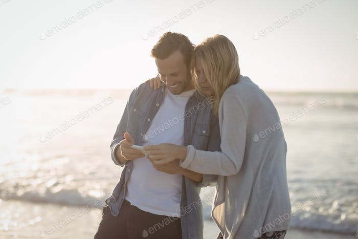 Happy couple using mobile phone at beach