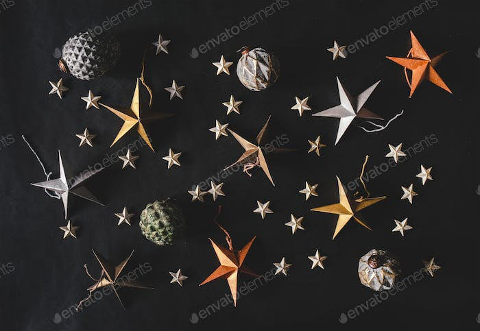 Christmas holiday decorative stars, cones and balls over black background