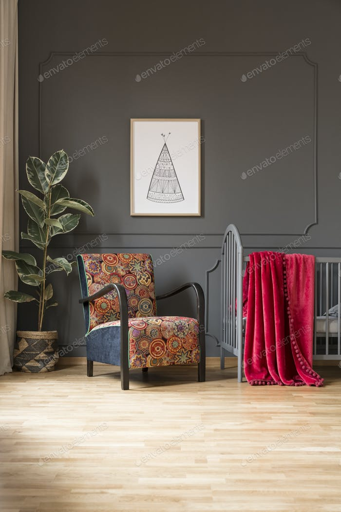 Patterned armchair next to bed with red blanket in baby's bedroo