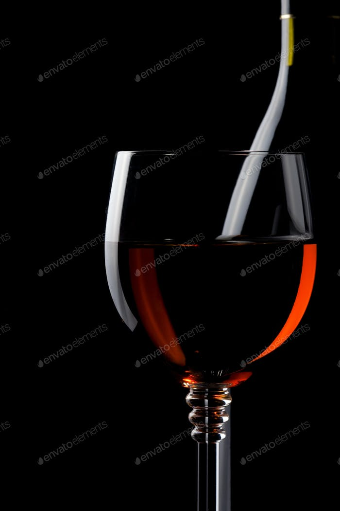 wine in glass and bottle on black