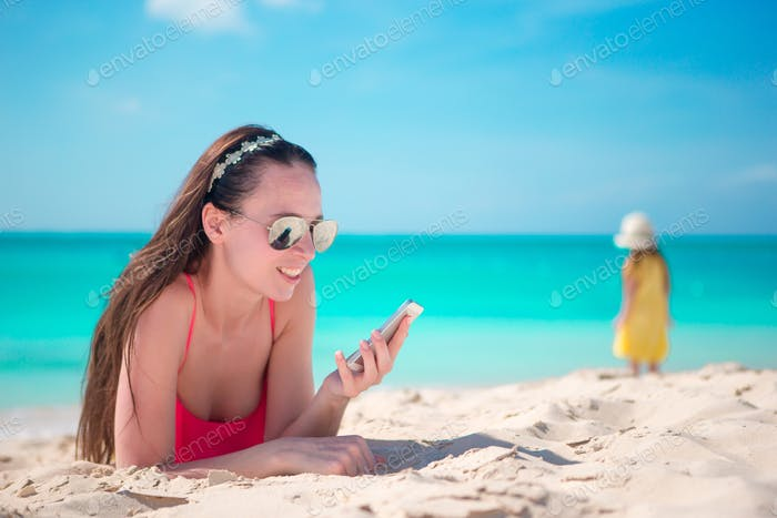 Young woman with cell phone at the beach