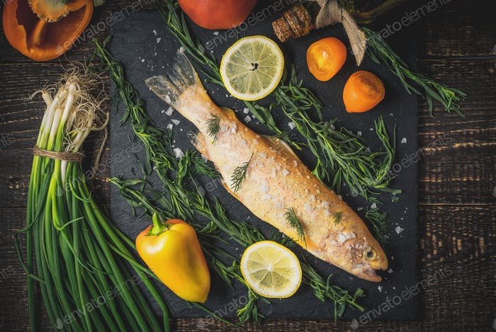 Raw golden trout with salt and vegetables on the wooden table top view