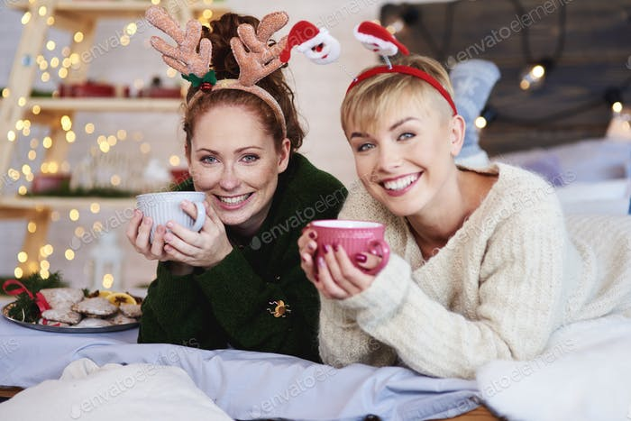 Two girls lying on bed and drinking tea