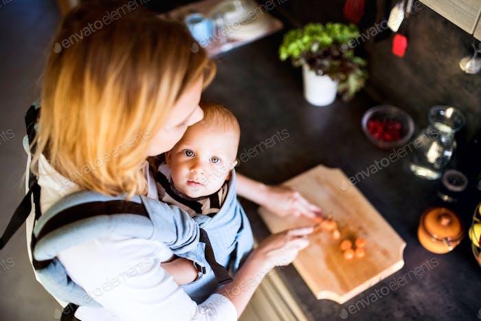 Joven madre con un Bebé haciendo las tareas domésticas.