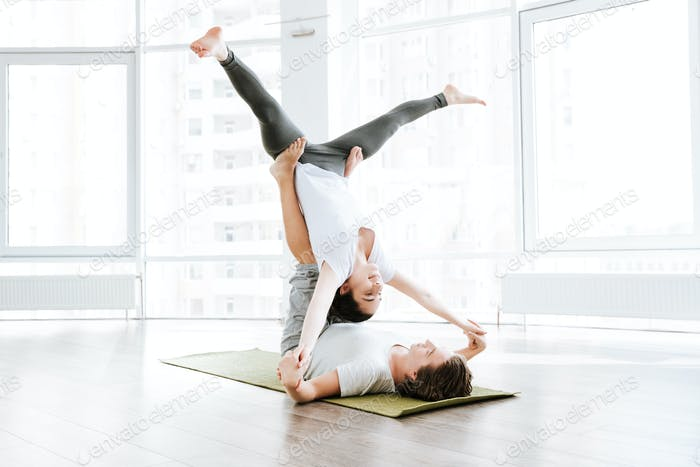 Happy young couple balancing and doing acro yog