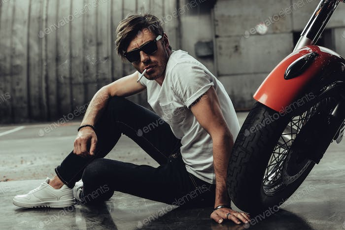 Handsome young man in sunglasses sitting near motorbike and smoking