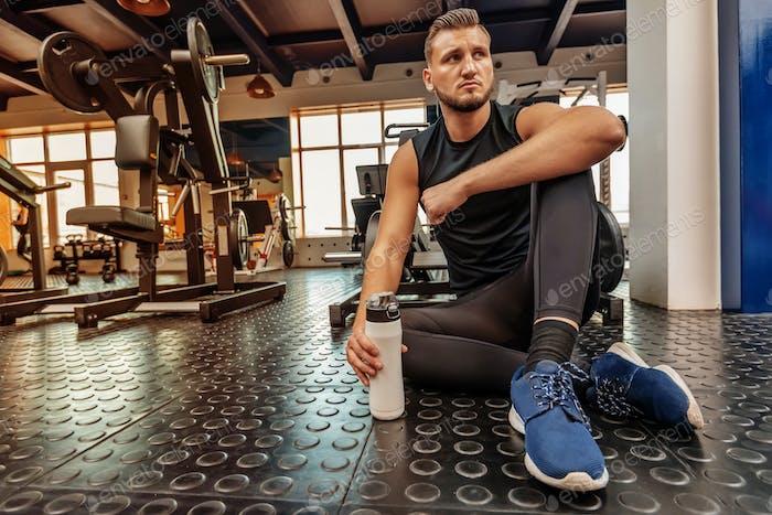 Männlicher Athlet sitzt mit Fitnessgetränk im modernen Fitnessstudio