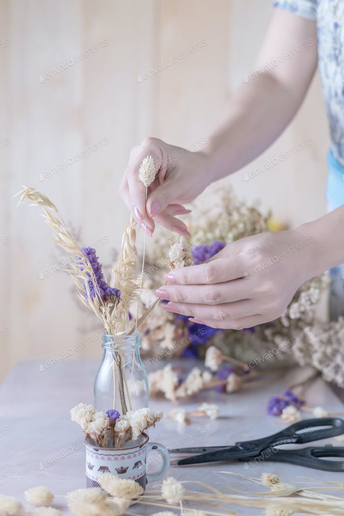 Cropped view hand of woman arrangement the flower in a glass vase