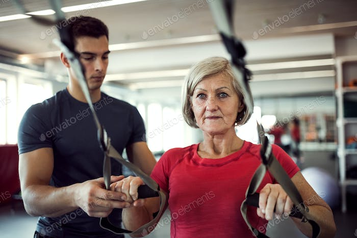 A senior woman in gym with a young trainer doing exercise with TRX.