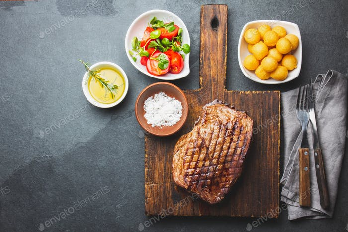Grilled beef steaks with spices on wooden cutting board.