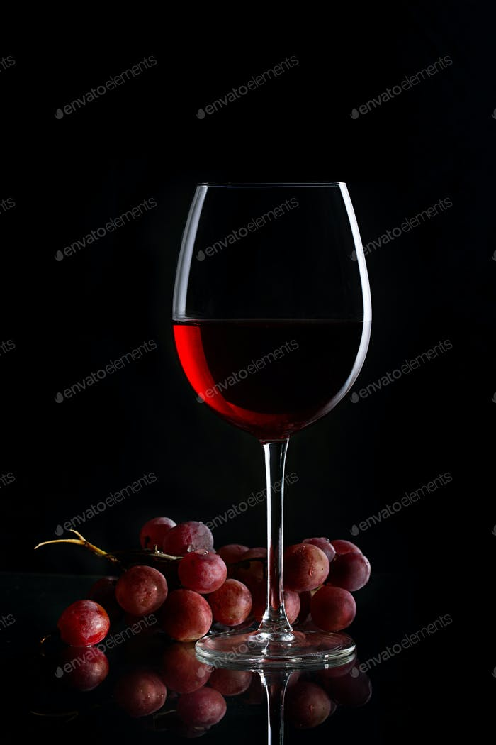 Glass of red wine and bunch of grapes on the dark background