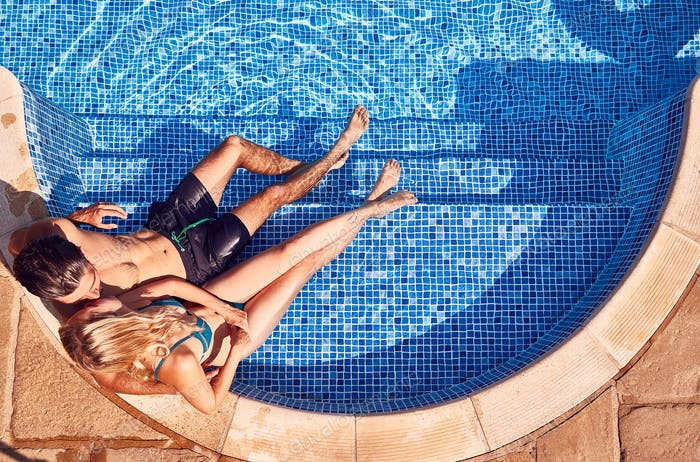 Overhead Shot Of Loving Couple In Swimsuits Relaxing In Outdoor Swimming Pool