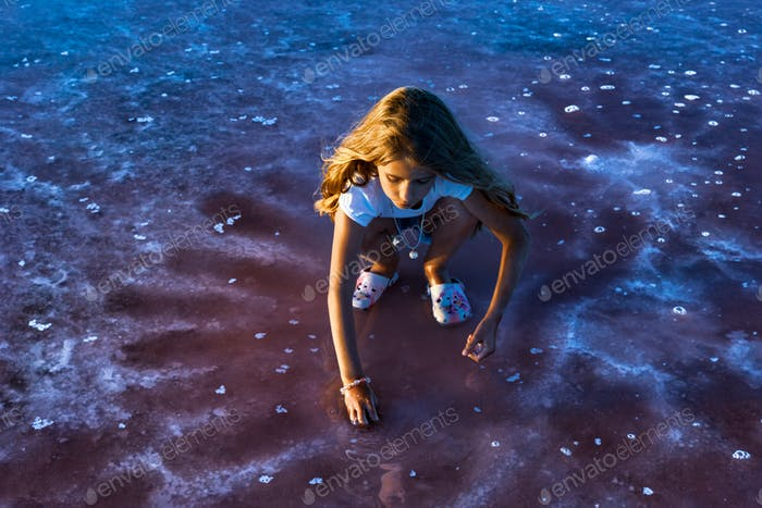 A little girl is looking at salt in a transparent water surface on a transparent background